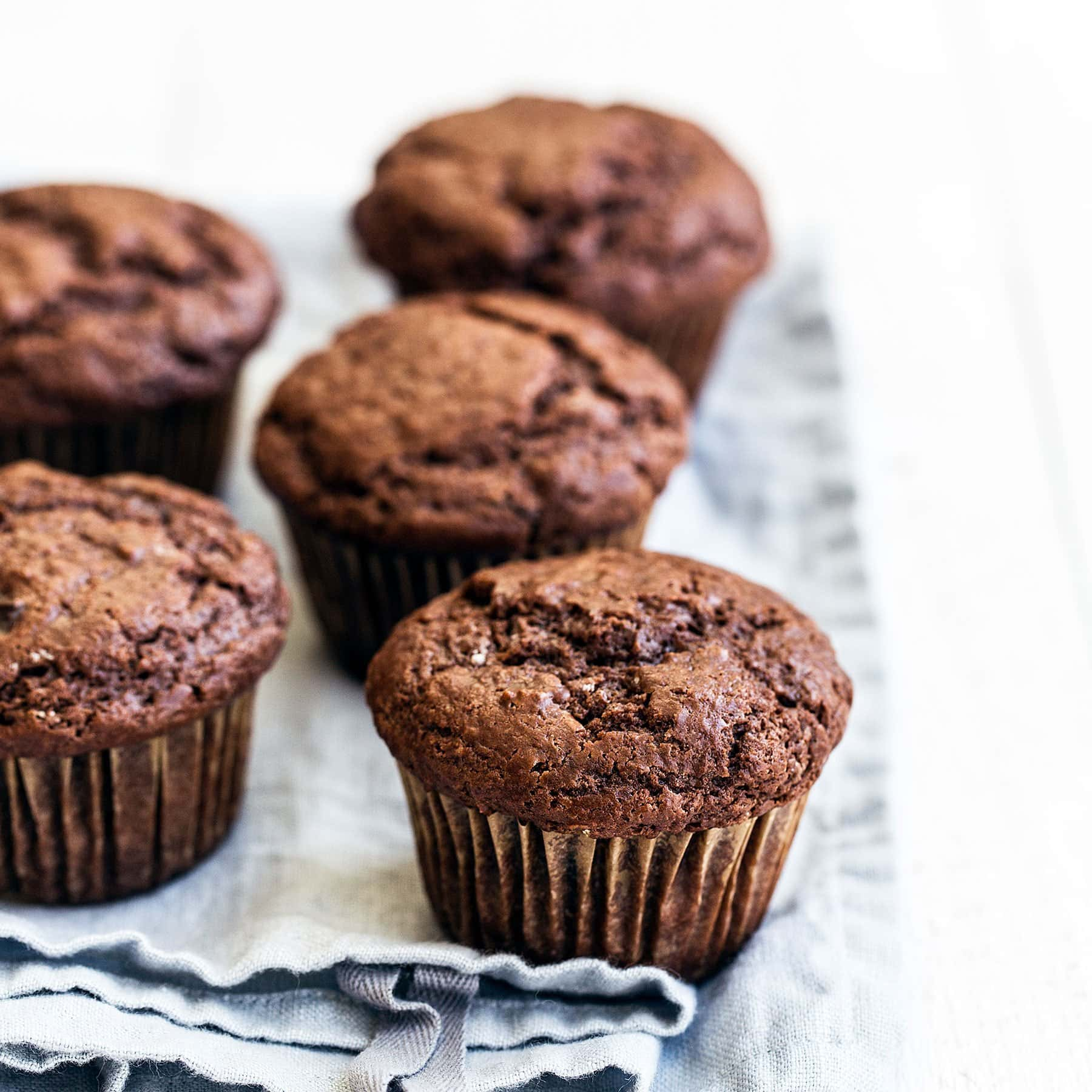 Moist and tender Double Chocolate Muffins feature a brown sugar cocoa muffin studded with gooey chocolate chunks for the ultimate easy treat!