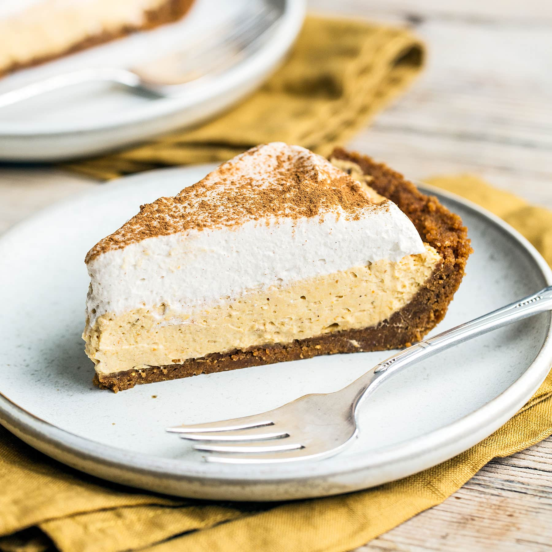 No Bake Pumpkin Mousse Pie features a thick Biscoff cookie crust filled with homemade pumpkin spice mousse and topped with fresh whipped cream. It's the ultimate easy pumpkin pie for Thanksgiving!