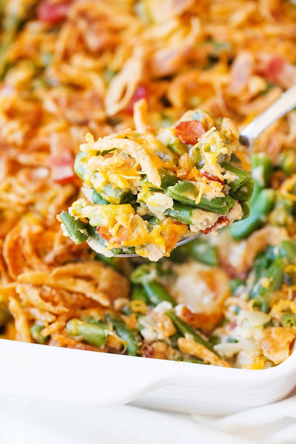 Scoop of cheesy green bean casserole with bacon in a white dish