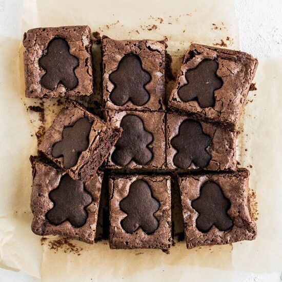 Gingerbread Brownies feature a thick and fudgy spiced brownie studded with crumbled gingerbread cookies and topped with adorable mini gingerbread men for a perfectly festive Christmas dessert!