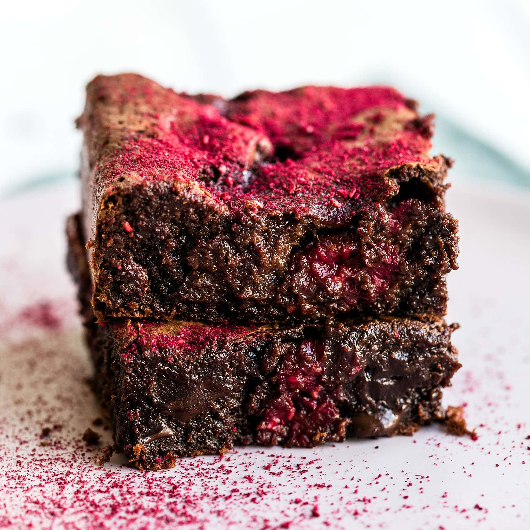 This Raspberry Brownie Recipe is ultra rich and fudgy with gooey chocolate chunks and fresh raspberries studded throughout. A dusting of freeze dried strawberries makes them absolutely beautiful and flavorful!
