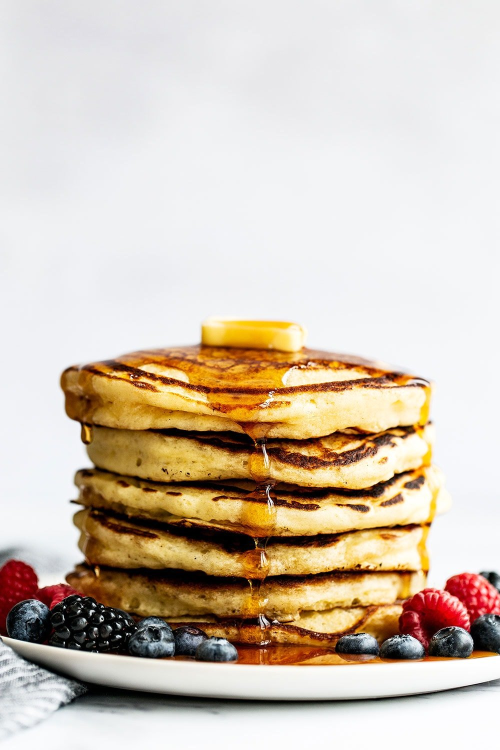 Tall stack of pancakes with butter, maple syrup, and berries