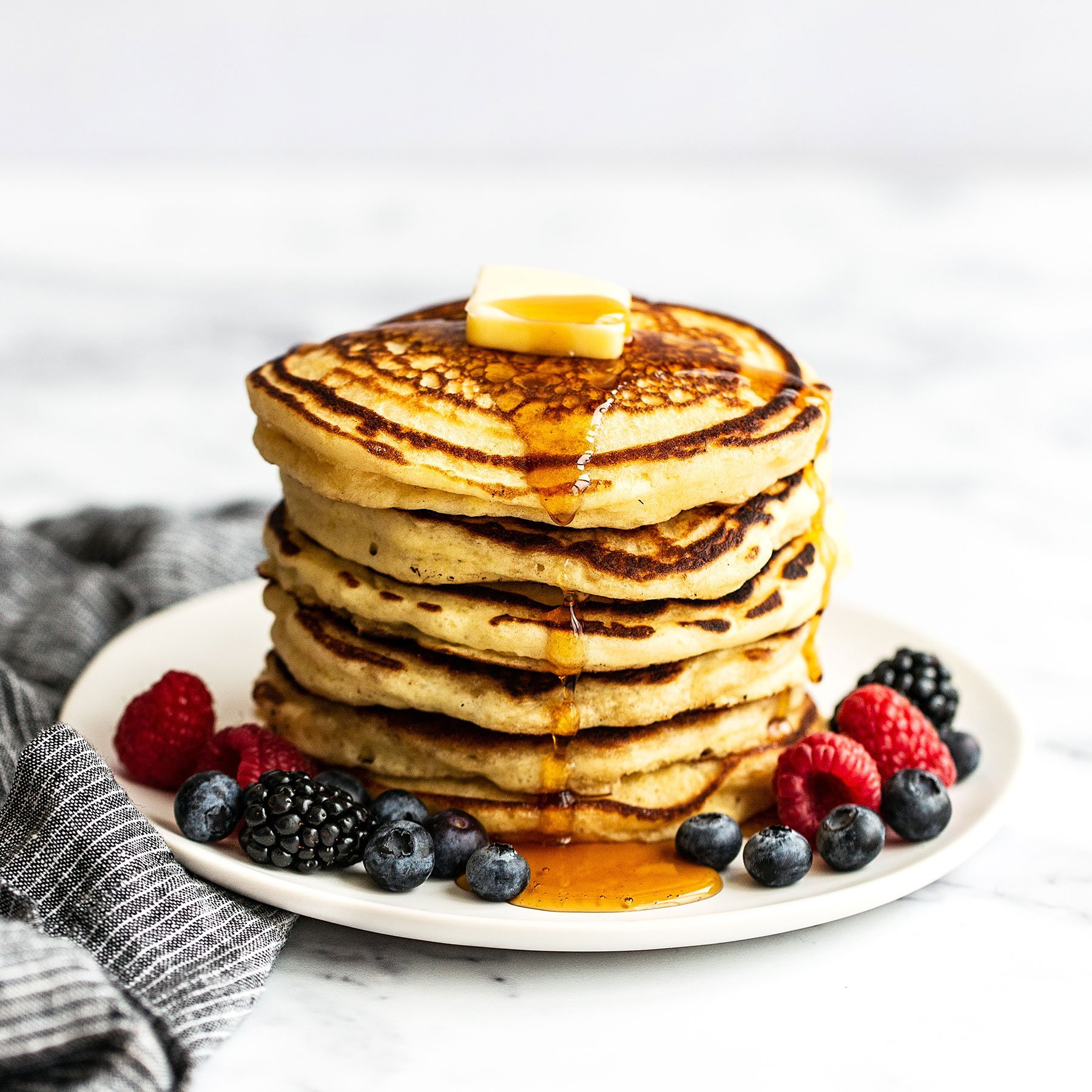 Tall stack of pancakes on a plate with syrup, berries, and a pat of butter