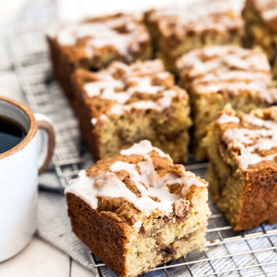 Multiple square pieces of coffee cake on a cooling rack near a cup of coffee