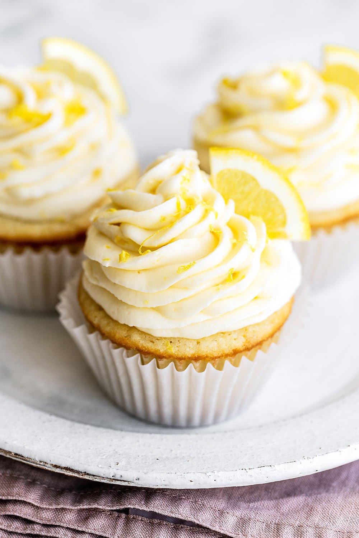 three lemon cupcakes on a plate