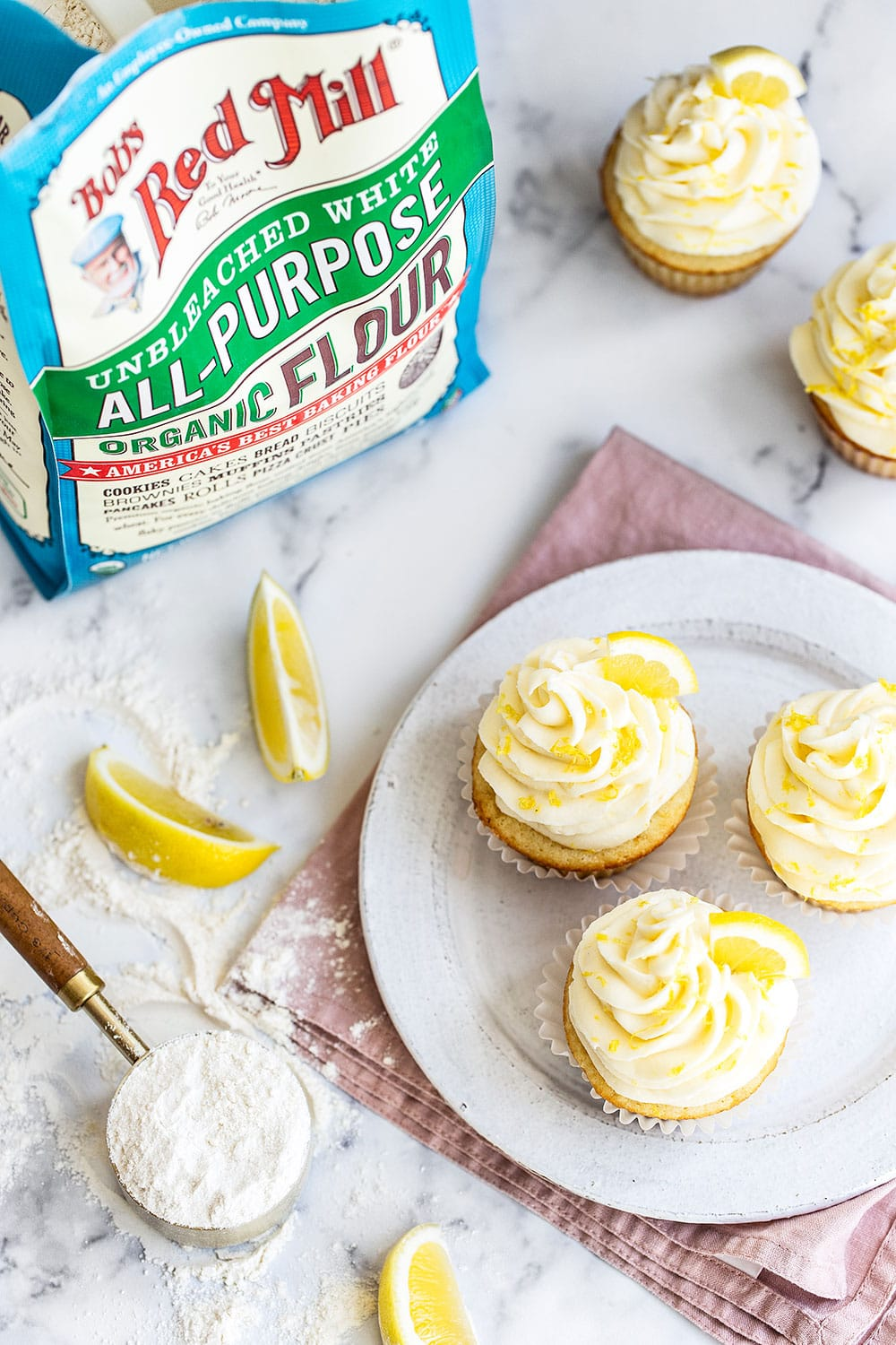 Lemon cupcakes with flour and ingredients on counter