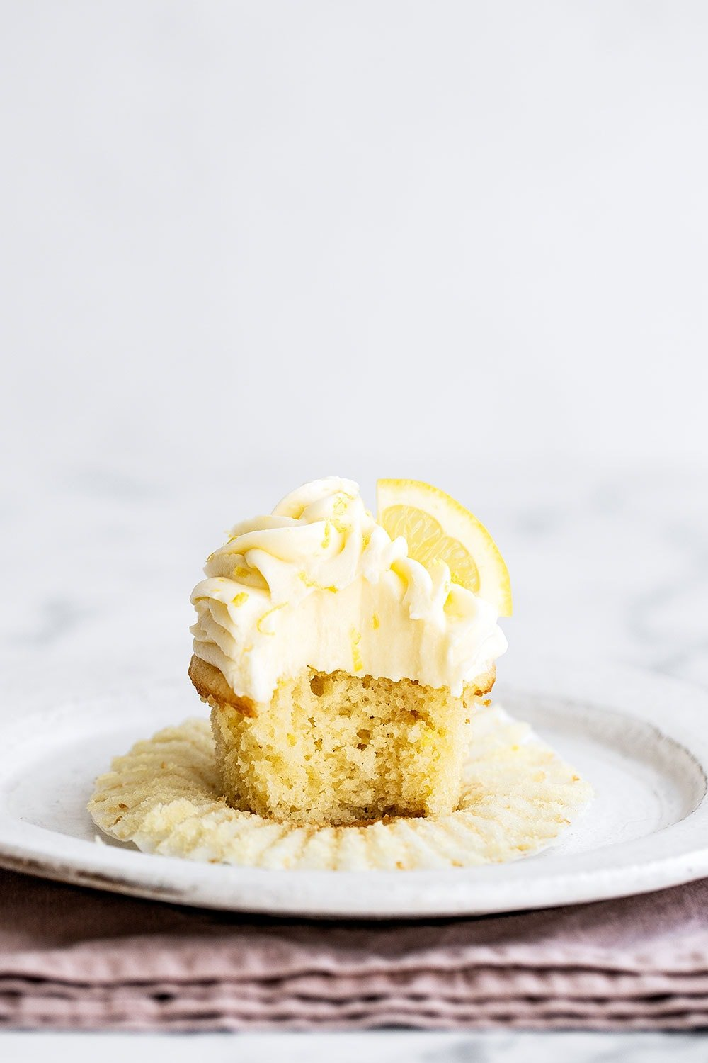 Lemon cupcake on a plate with cupcake liner removed
