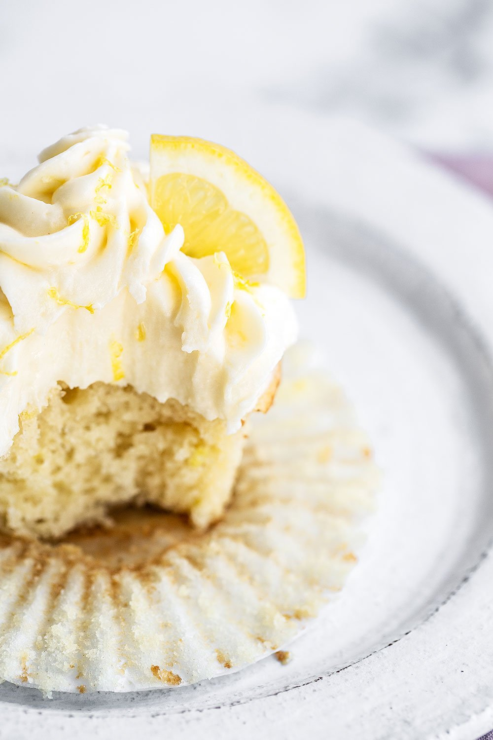 Lemon cupcake on plate with bite taken out