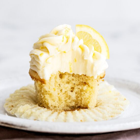 lemon cupcake on a plate with bite taken out