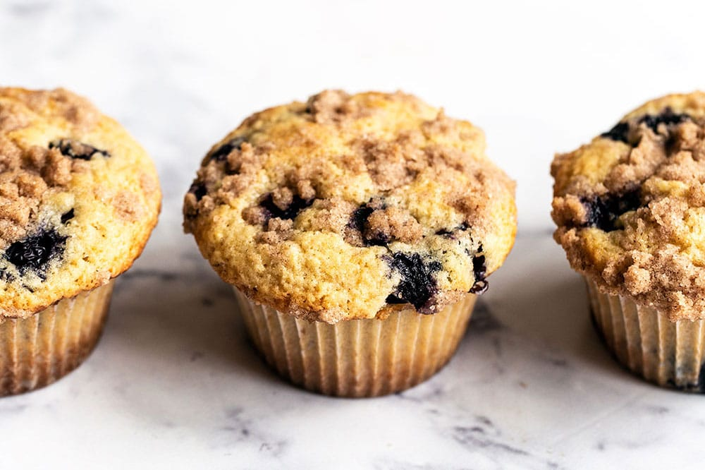Three homemade blueberry muffins with brown butter and crumb topping