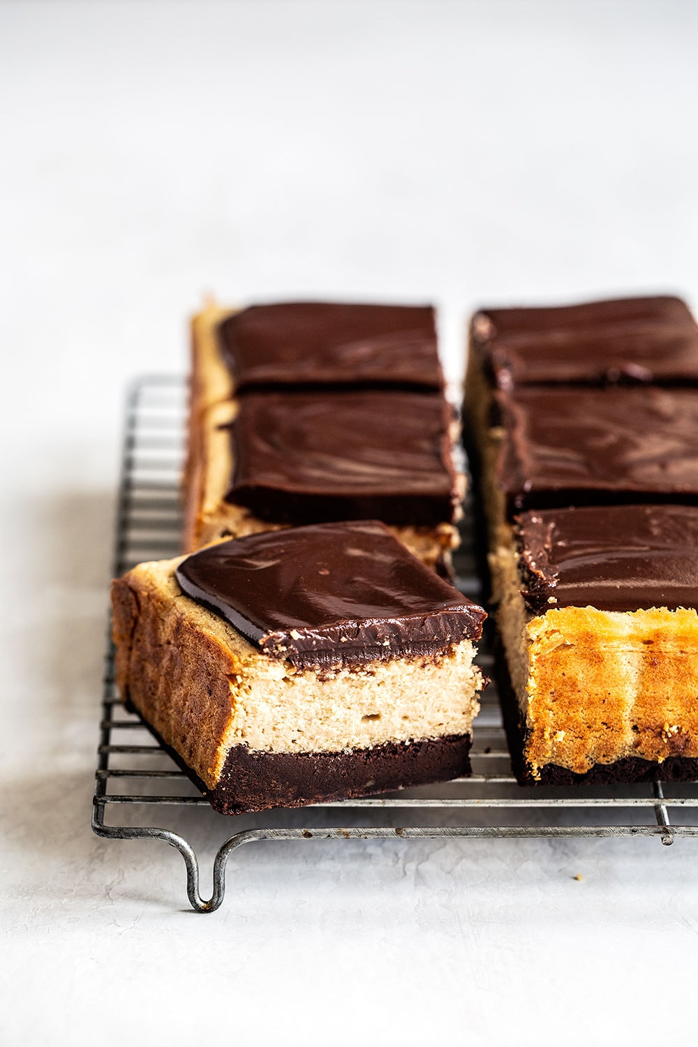 Peanut Butter Cheesecake Brownie Bars with ganache on a cooling rack