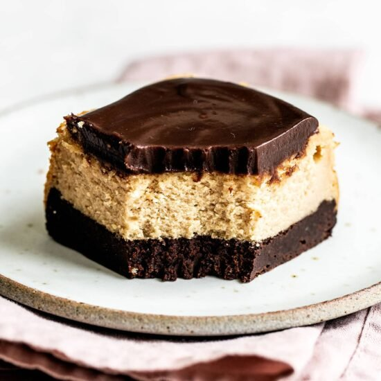 Brownie bottom peanut butter cheesecake bar with bite taken out
