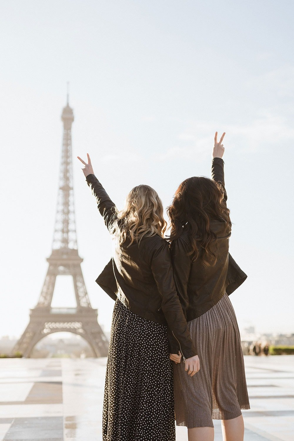 Two girls standing in front of the Eiffel Tower at sunrise
