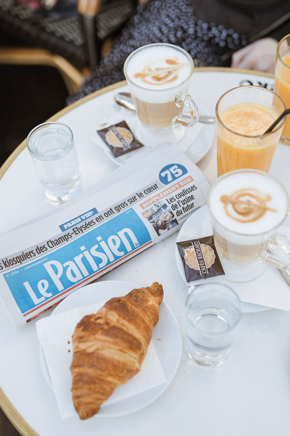 Croissants, coffee, and newspaper on cafe table in paris