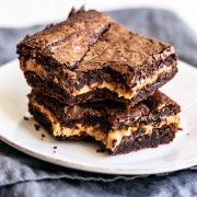 Peanut butter stuffed brownies stacked on top of each other on a plate