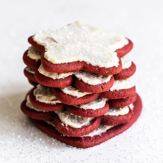 Stack of red velvet cut out cookies with cream cheese frosting