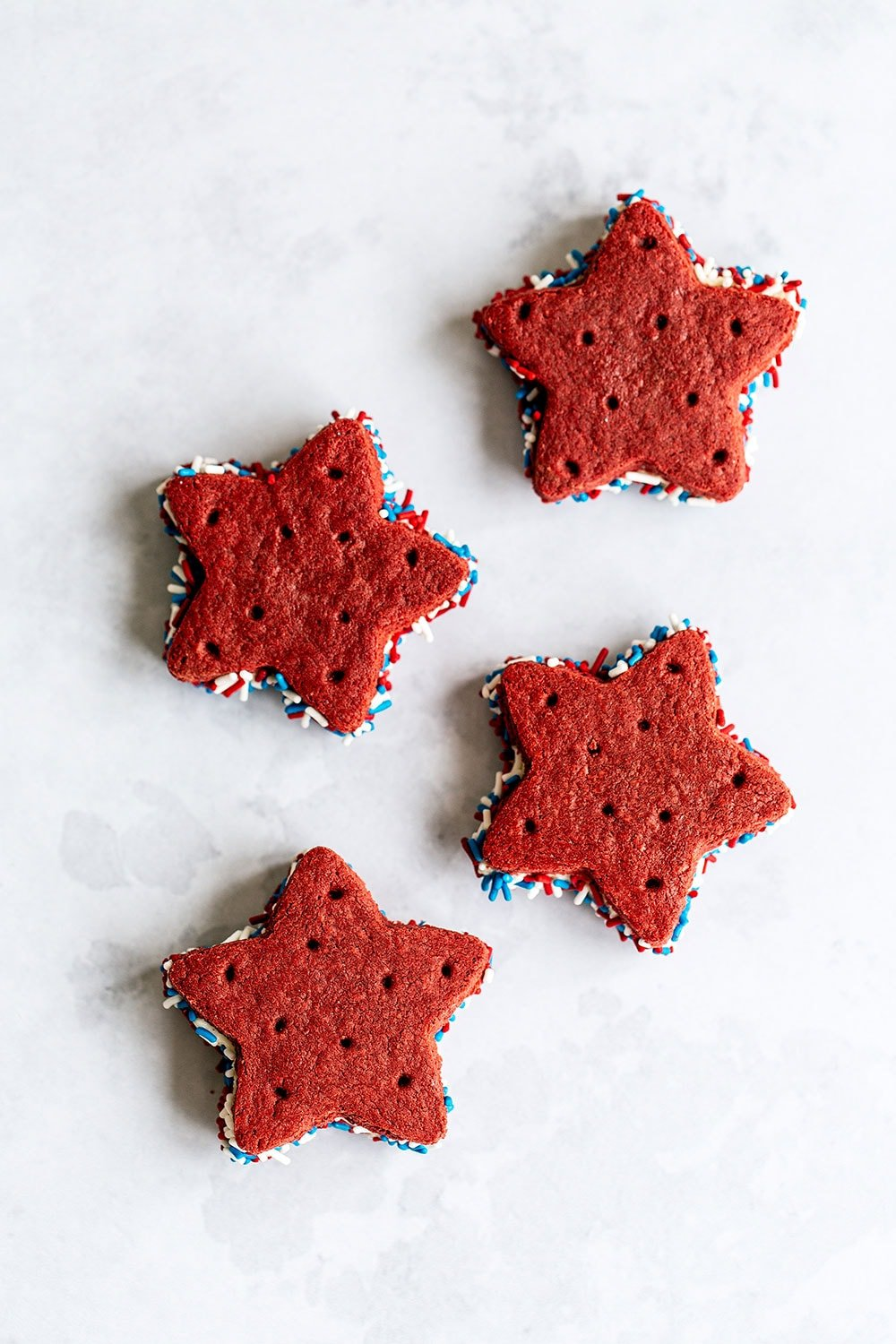 Easy red velvet ice cream sandwiches with homemade cookies on a marble surface