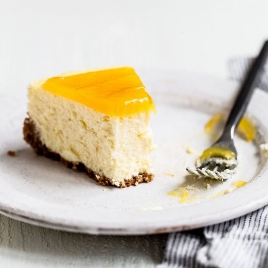 Slice of homemade lemon cheesecake with graham cracker crust on a plate with a fork