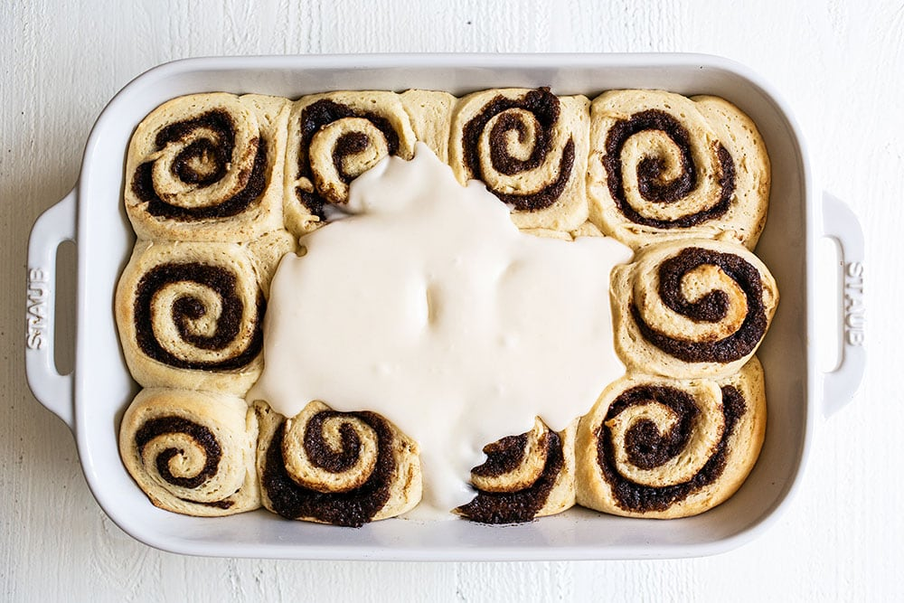 Spreading icing on homemade cinnamon buns