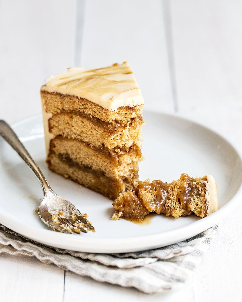 Ultra rich, tender, and moist Butterscotch layer cake slice on a plate with a bite taken out