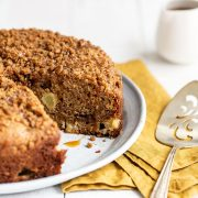 Easy caramel apple coffee cake on a platter with a serving spoon and a slice already removed