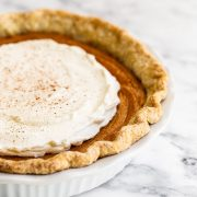 Homemade Brown butter sweet potato pie with whipped cream on a marble counter