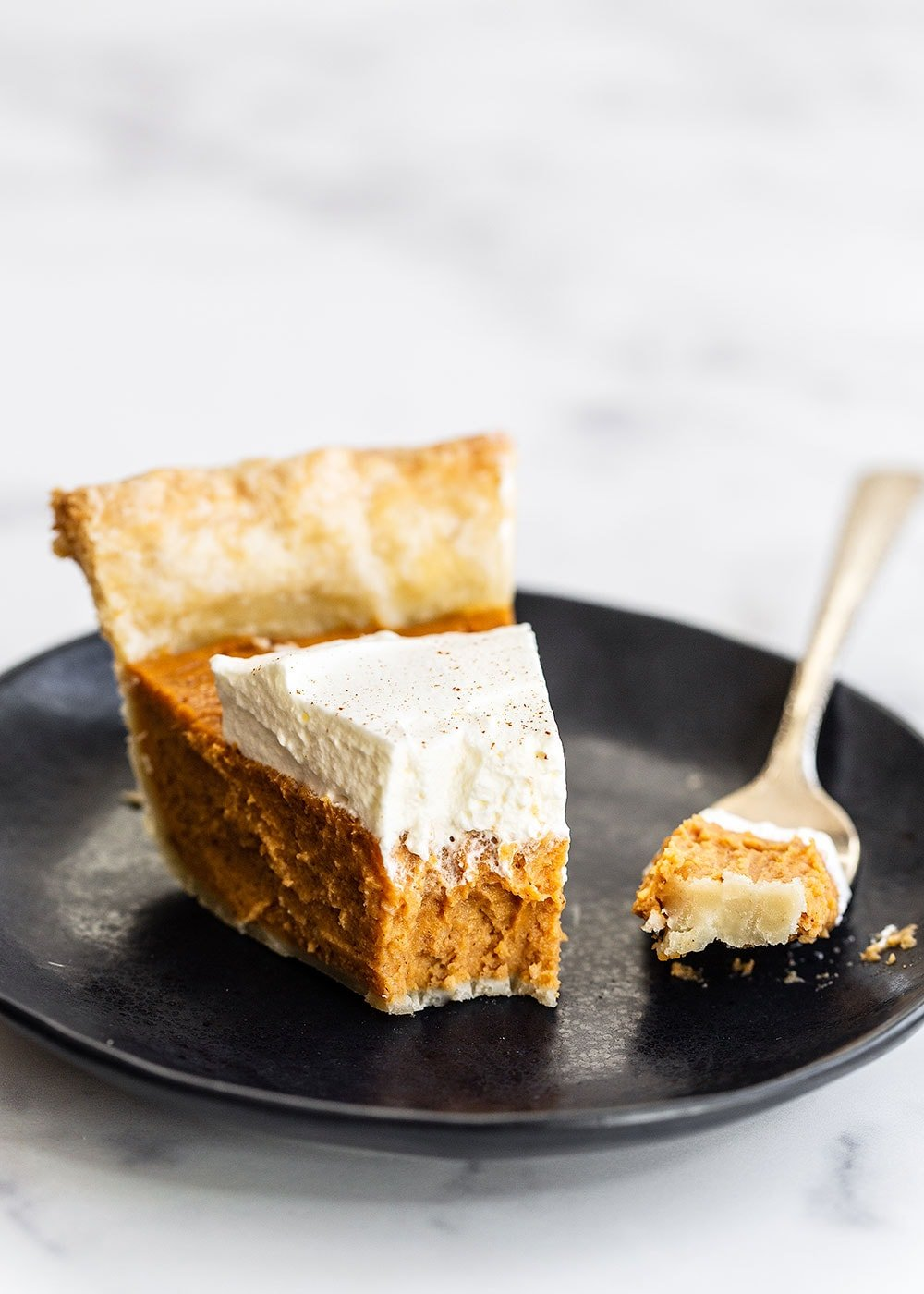 Slice of sweet potato pie with a bite taken out and whipped cream on top