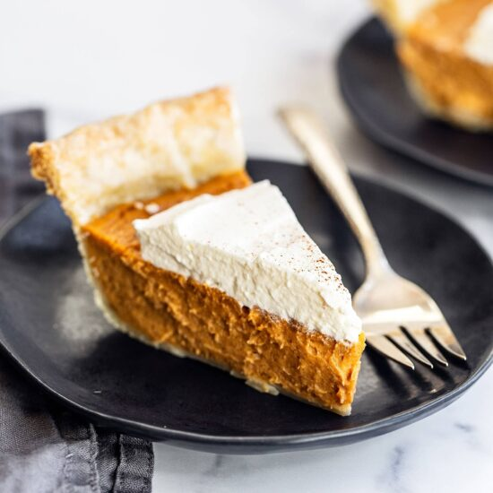 Slice of homemade brown butter sweet potato pie on a plate with a fork