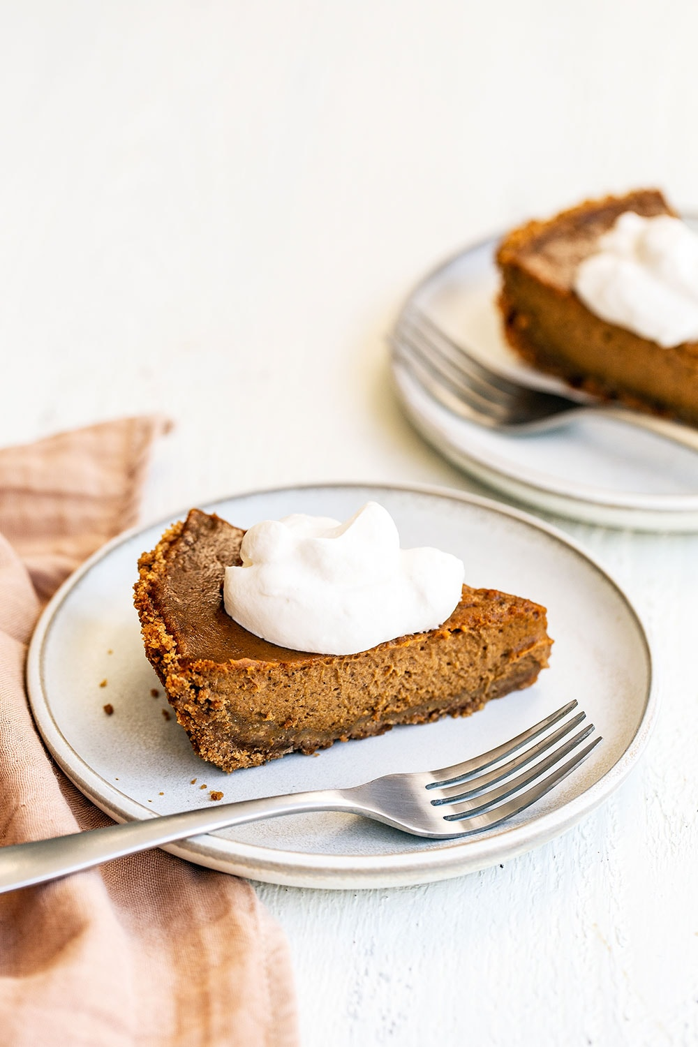 Slice of easy pumpkin pie on a plate with a dollop of whipped cream on top