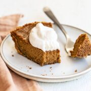 Slice of easy pumpkin pie with graham cracker crust and whipped cream on top