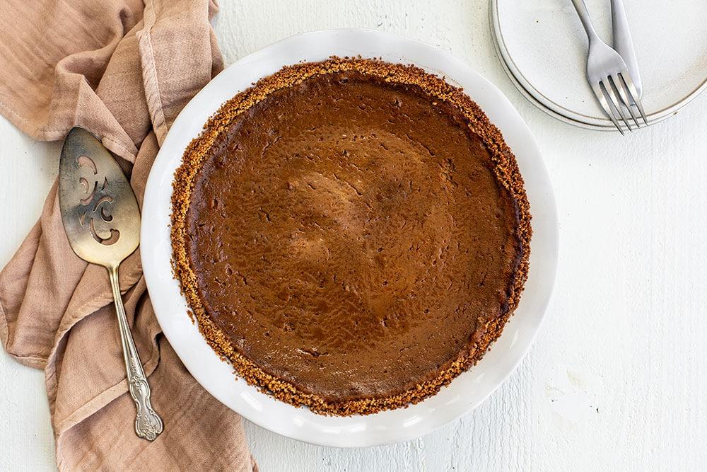 Pumpkin pie with graham cracker crust in a ceramic pie dish