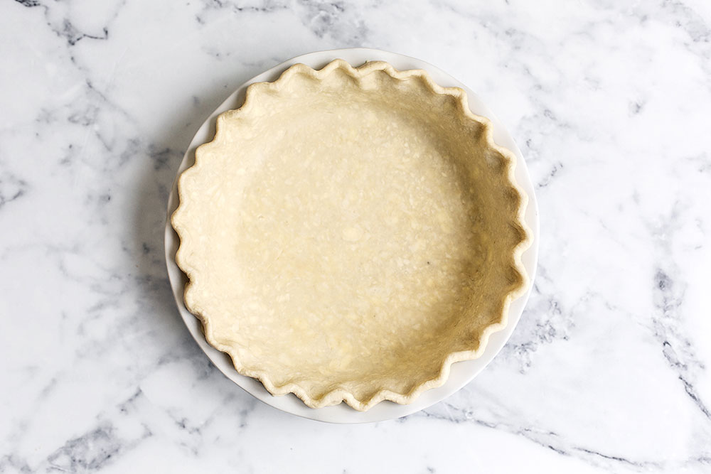 Homemade all butter pie crust in pie tin ready to be par baked