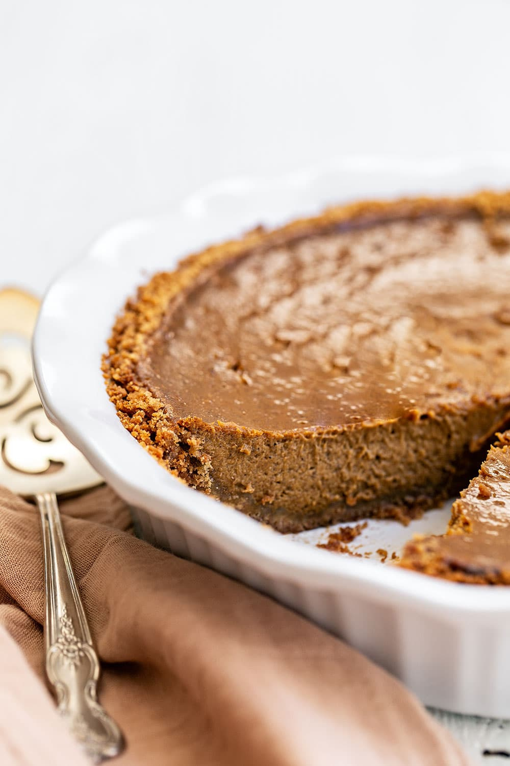 Quick and easy pumpkin pie in a pie dish with a slice removed