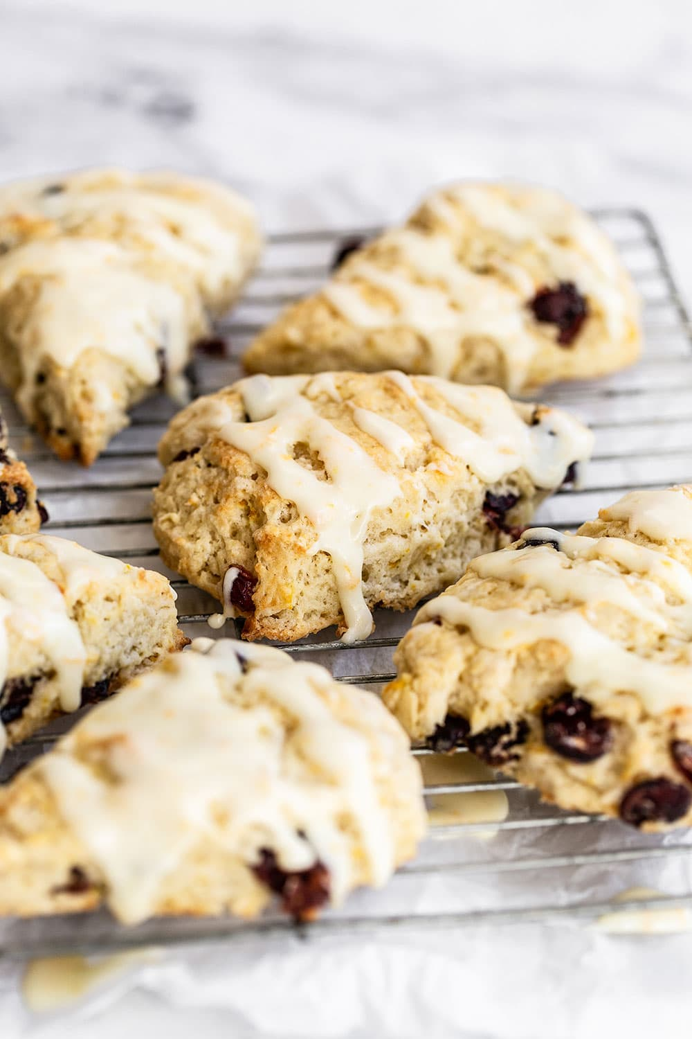 Cranberry orange scones on a cooling rack with icing setting