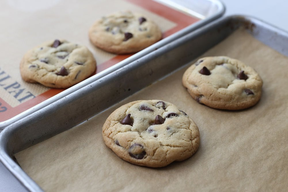 Four cookies side by side to compare silpat vs parchment paper