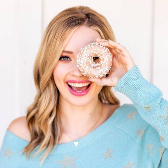 Photo of Tessa holding a vanilla donut