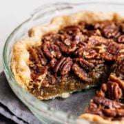 Pecan pie in pie plate with a slice removed
