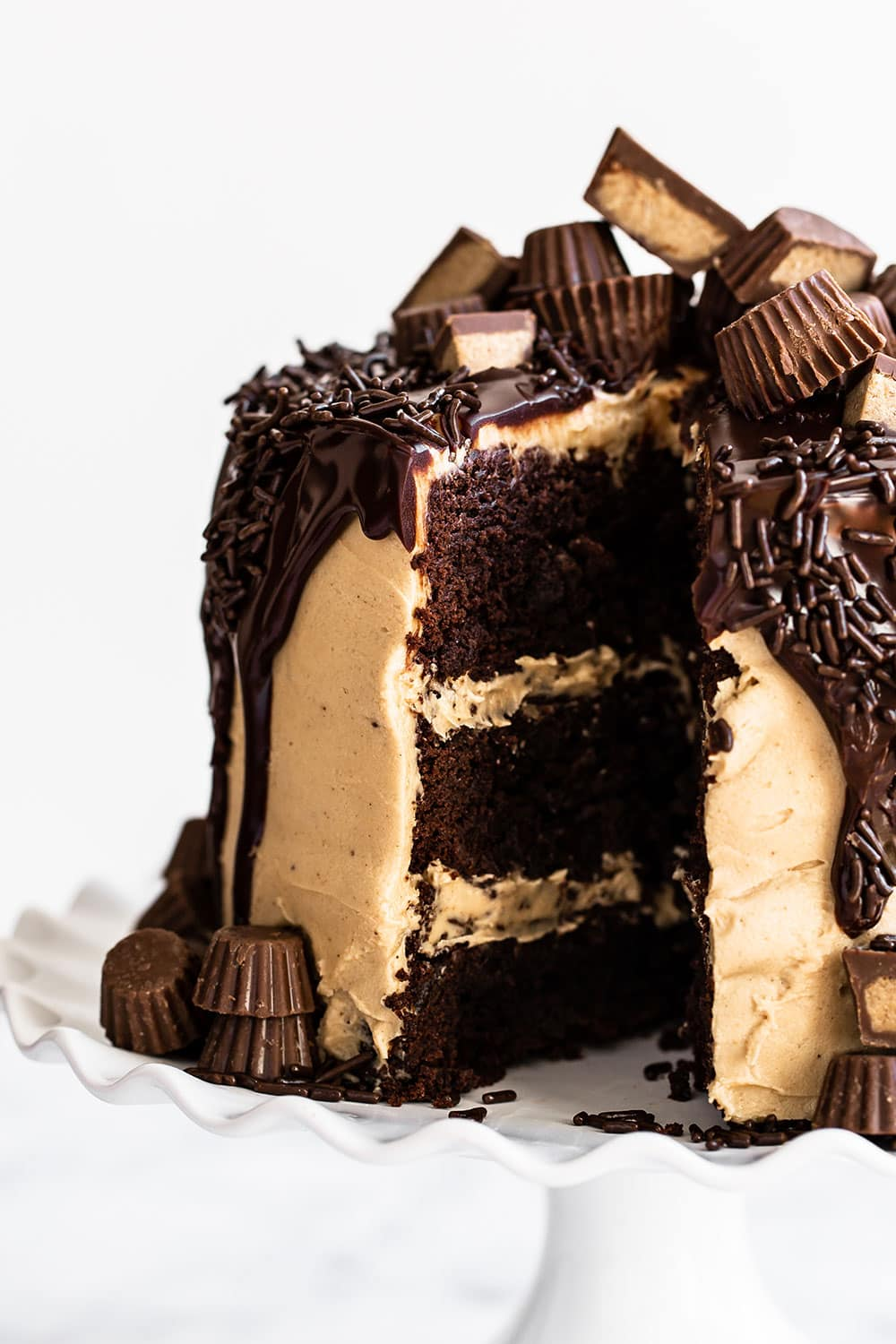 Peanut butter brownie cake on a cake stand topped with dipping chocolate ganache and peanut butter cups with a slice taken out