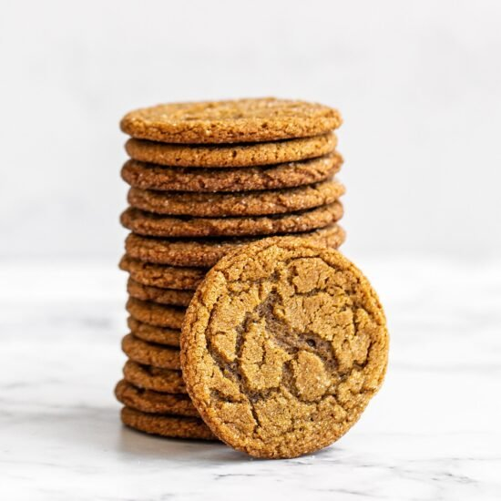 Stack of thin and crispy gingersnap cookies on a marble counter
