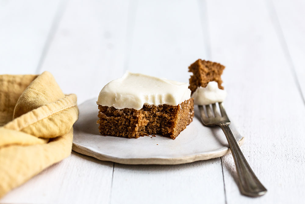 Slice of gingerbread sheet cake with a bite removed