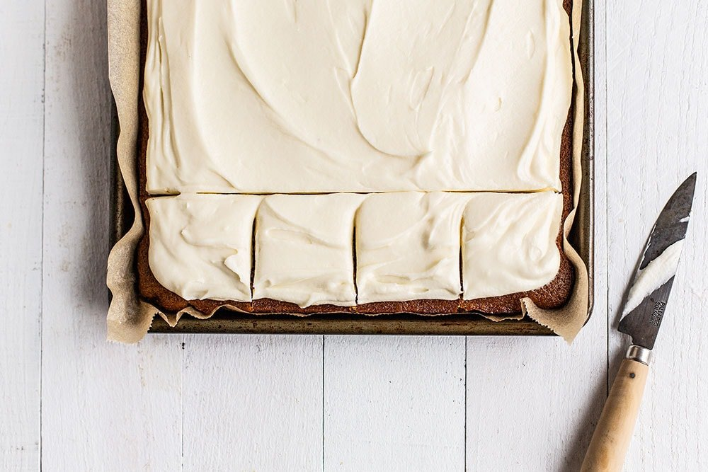 Gingerbread sheet cake in a baking pan with slices cut ready to serve