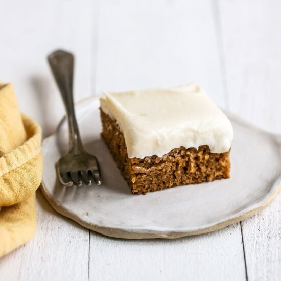 Slice of gingerbread sheet cake with cream cheese frosting on a plate