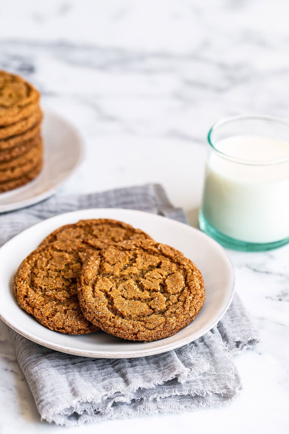 Crunchy gingersnaps on a plate with a glass of milk