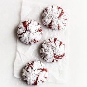 Red velvet crinkle cookies on parchment paper with a snowy coating of powdered sugar