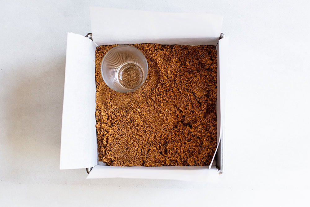 Graham cracker crust being pressed into a baking pan with a cup