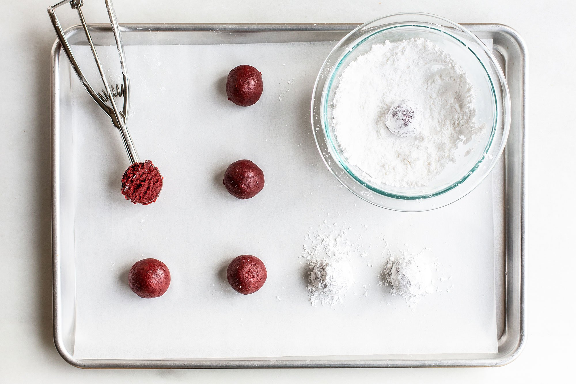 red velvet crinkle cookie dough rolled into balls and being coated in powdered sugar