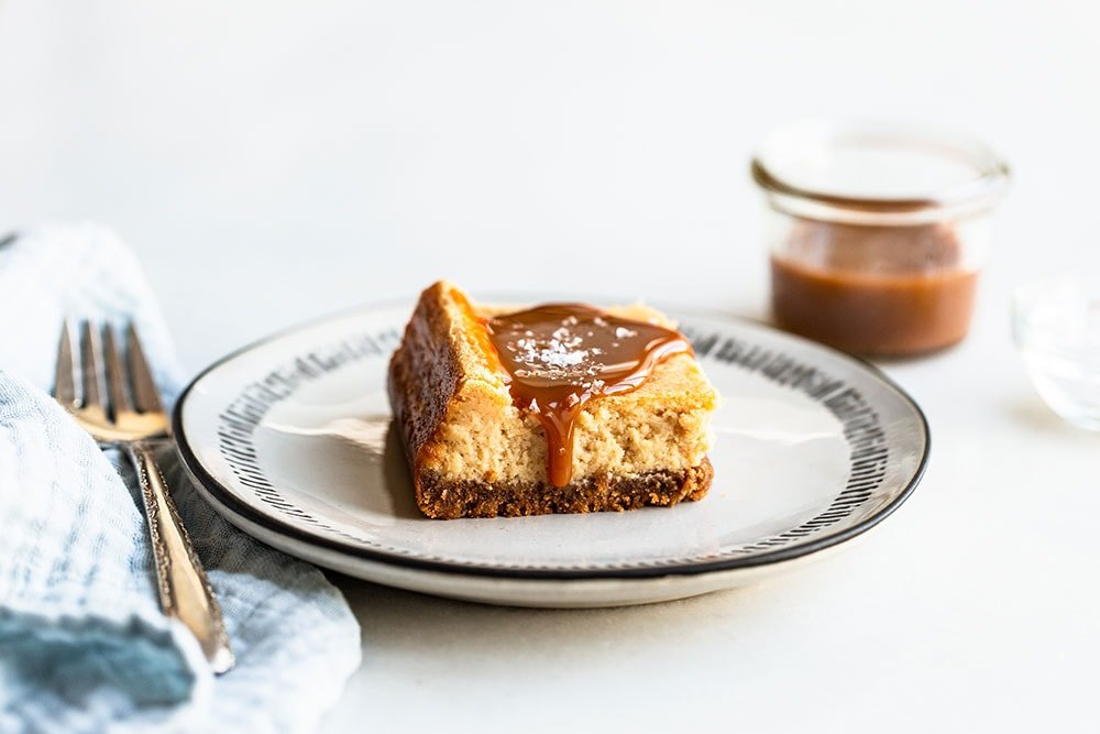 Salted caramel cheesecake bar on a plate with a bite taken out