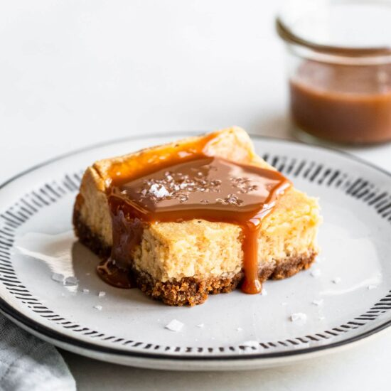Salted caramel cheesecake square on a plate with caramel sauce on top