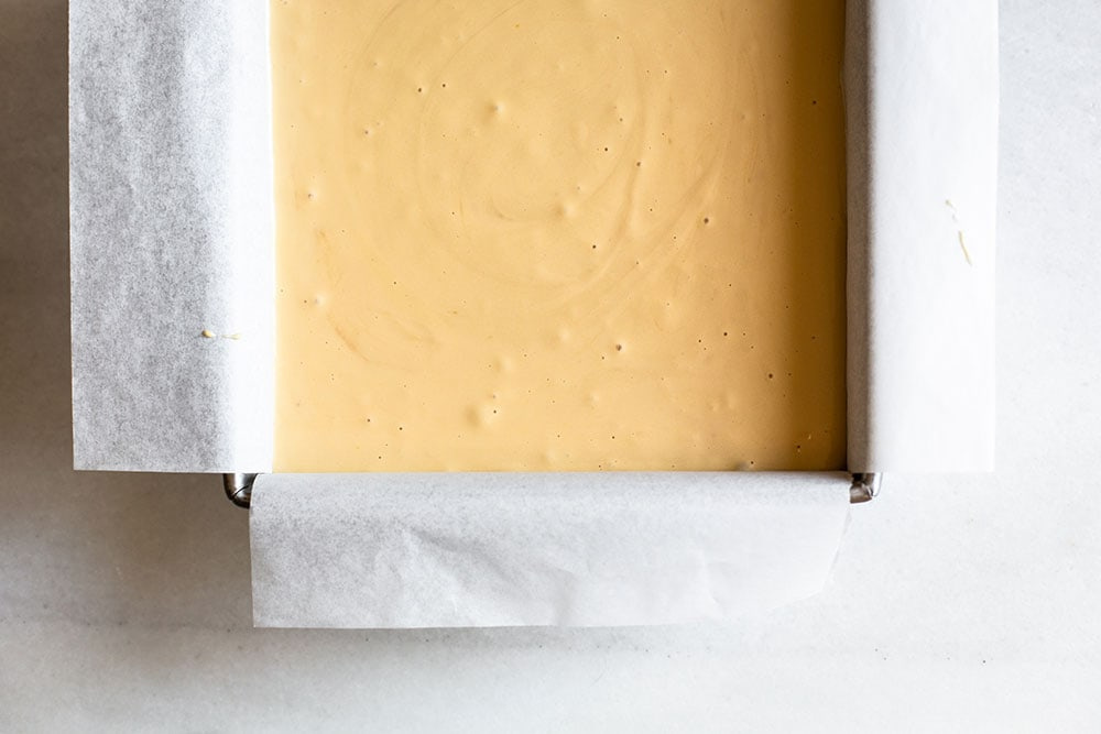 Cheesecake batter in square pan ready to be baked
