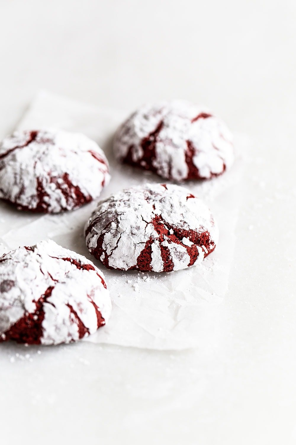 Easy red velvet crinkle cookies on a piece of parchment paper